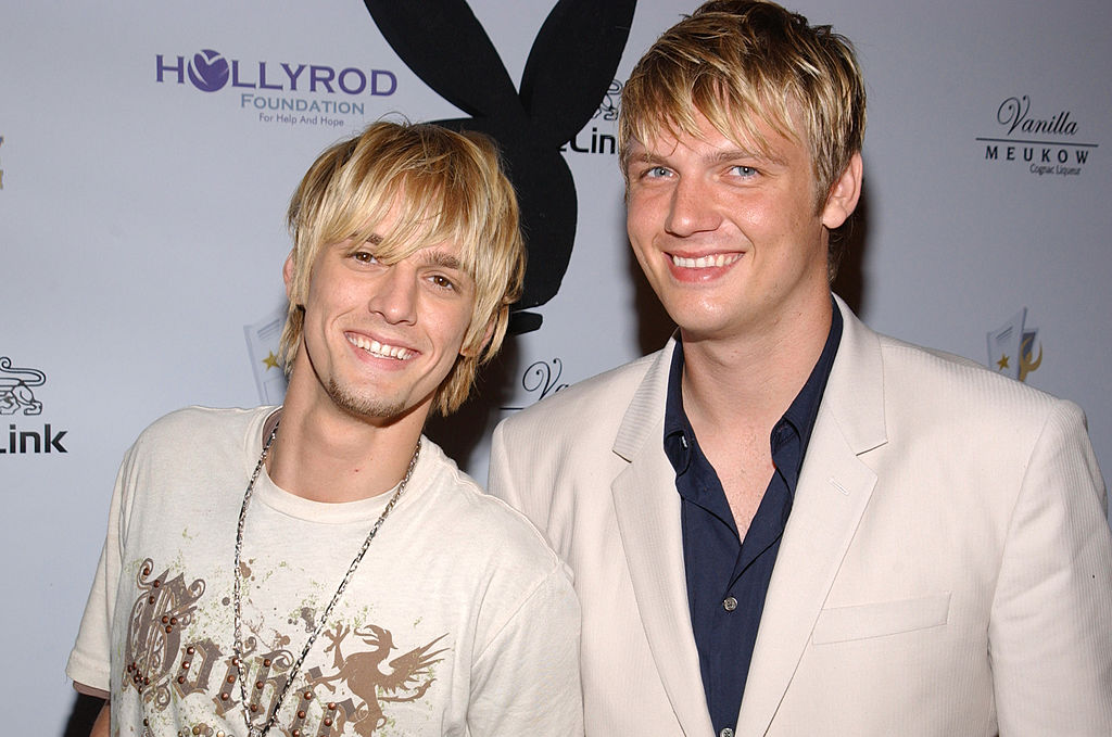 Aaron Carter and Nick Carter smiling in front of a repeating background