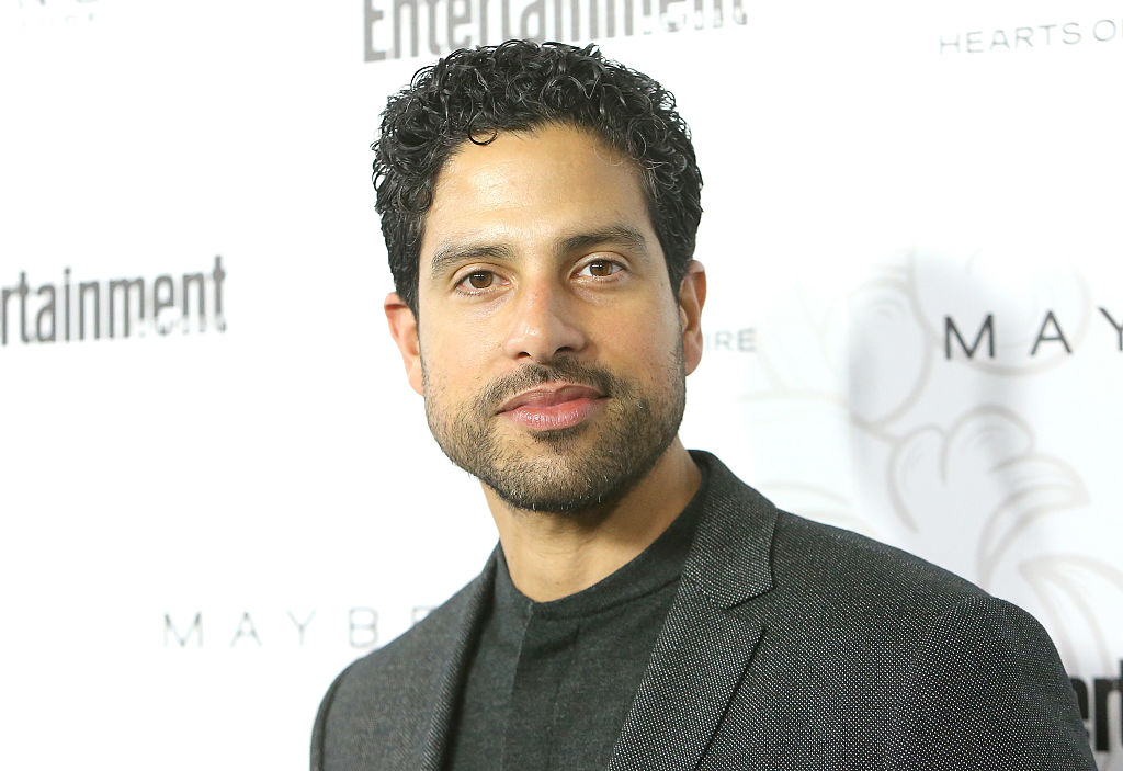 Adam Rodriguez smiling in front of a repeating background