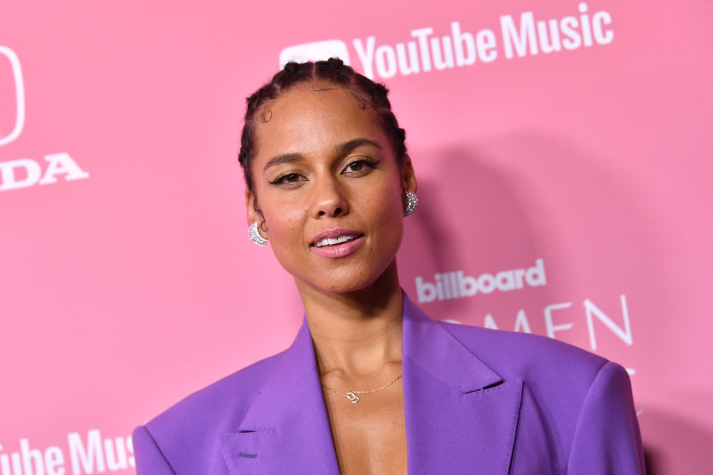 Alicia Keys smiling in front of a repeating pink and white background
