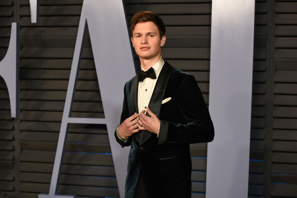 Ansel Elgort in a jacket in front of a repeating background