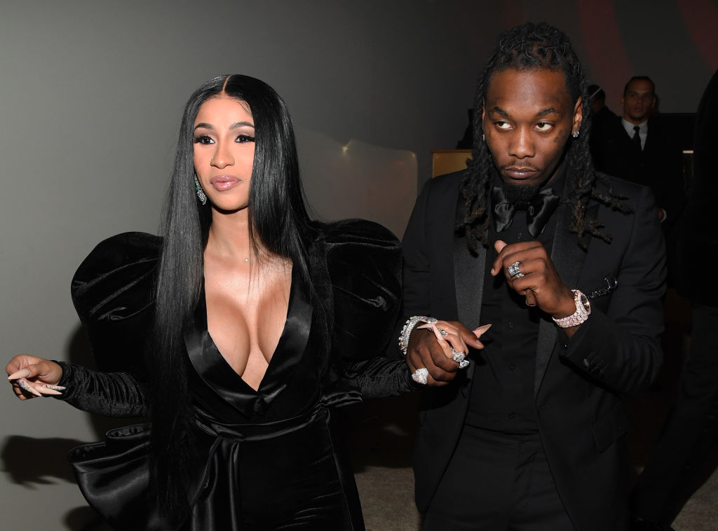 Cardi B and Offset in black outfits smiling, looking away from the camera
