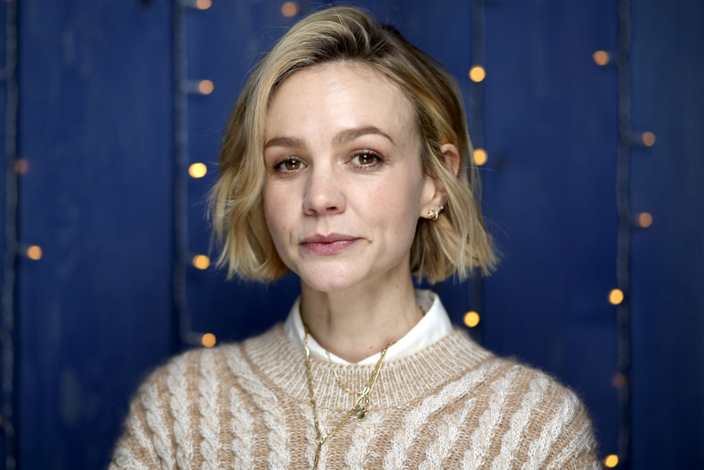 Carey Mulligan smiling in front of a dark blue wall