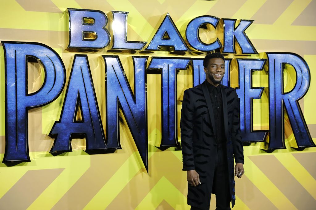 Chadwick Boseman smiling in front of the Black Panther logo