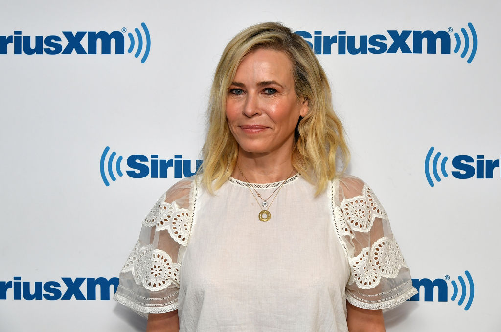 Chelsea Handler smiling in front of a repeating background