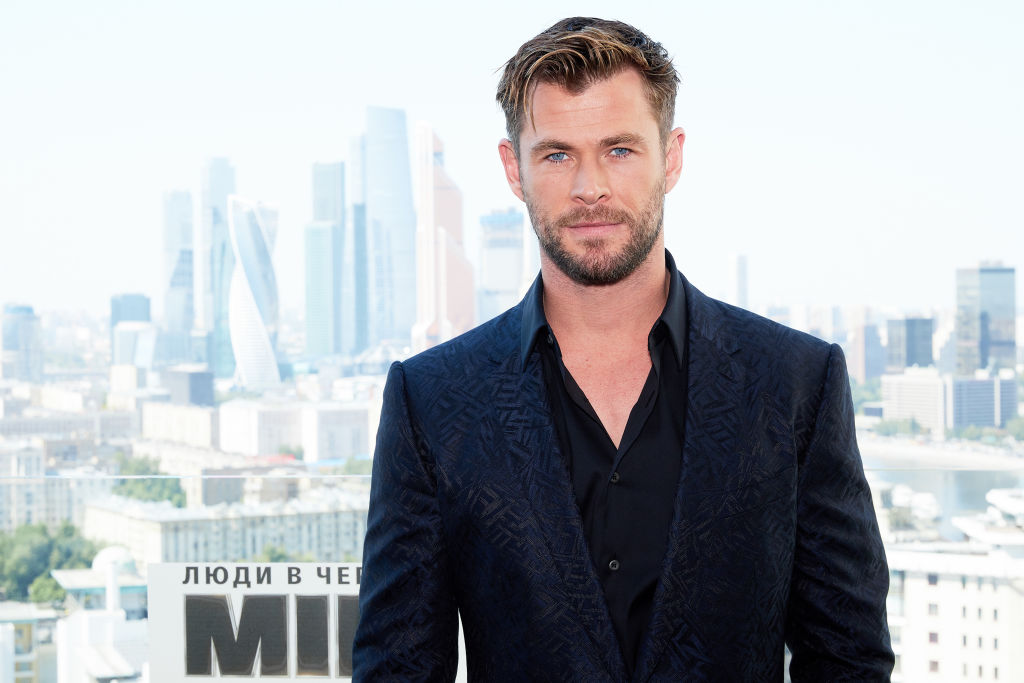 Chris Hemsworth smiling in front of a cityscape