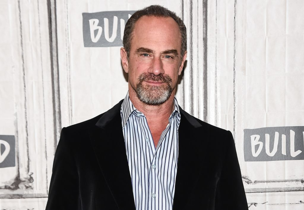 Christopher Meloni smiling in front of a repeating background