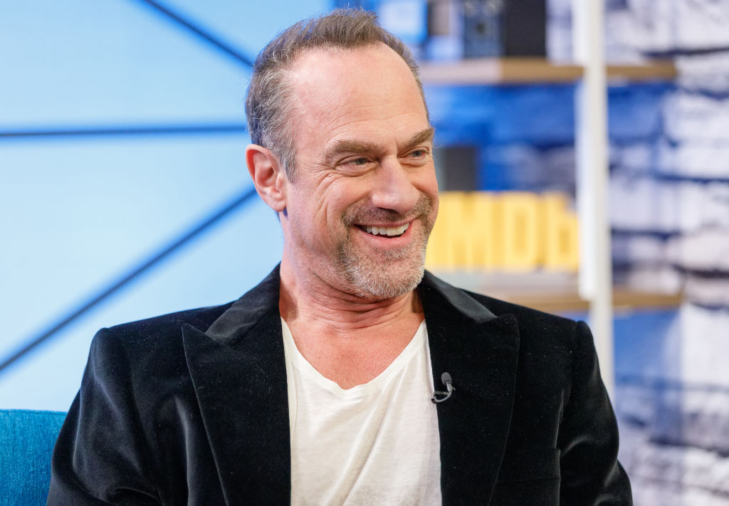 Christopher Meloni smiling with his head turned away from the camera