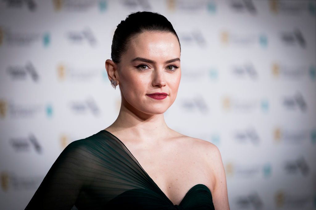 Daisy Ridley smiling in front of a repeating background