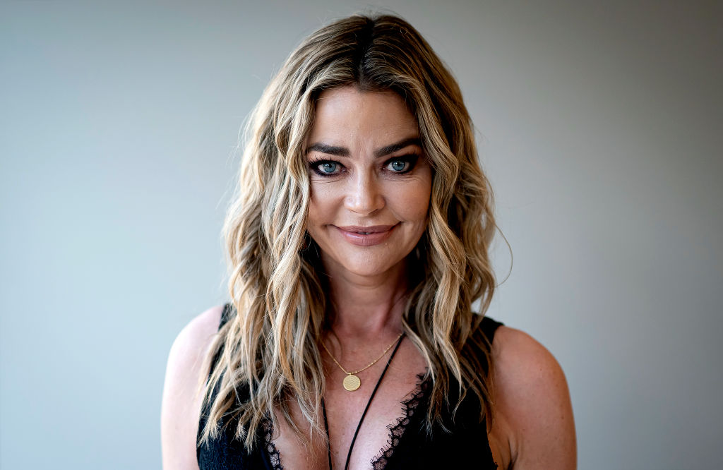 Denise Richards smiling in front of a white backgrounds