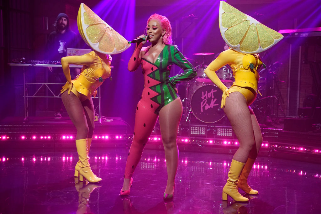 Doja Cat in a watermelon themed jumpsuit with two dancers wearing lemon wedges over their heads