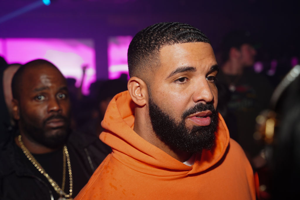 Drake in an orange sweatshirt looking off camera