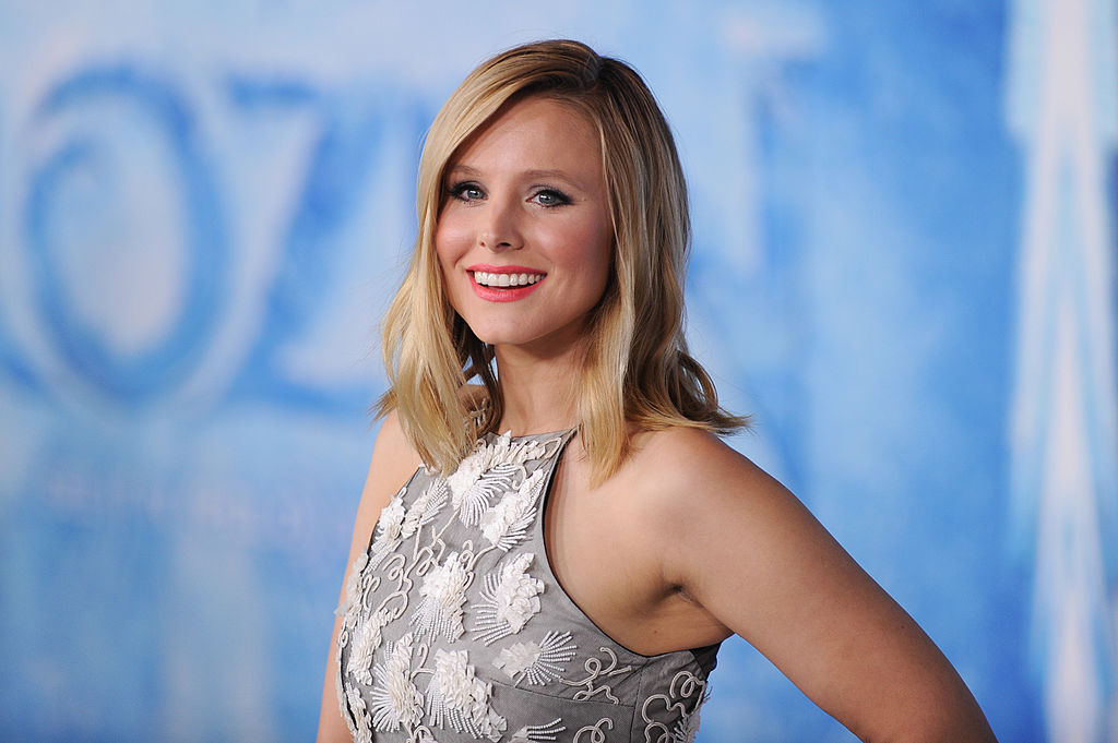 Kristen Bell smiling in front of blue and white background