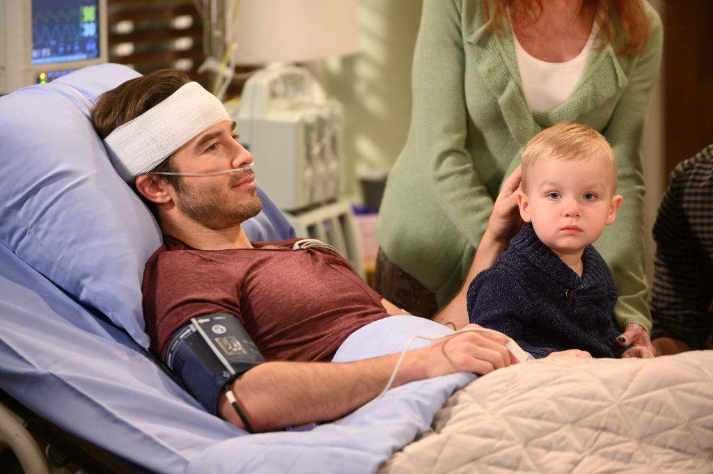 Lucas (Ryan Carnes) in a hospital bed with a baby on his lap