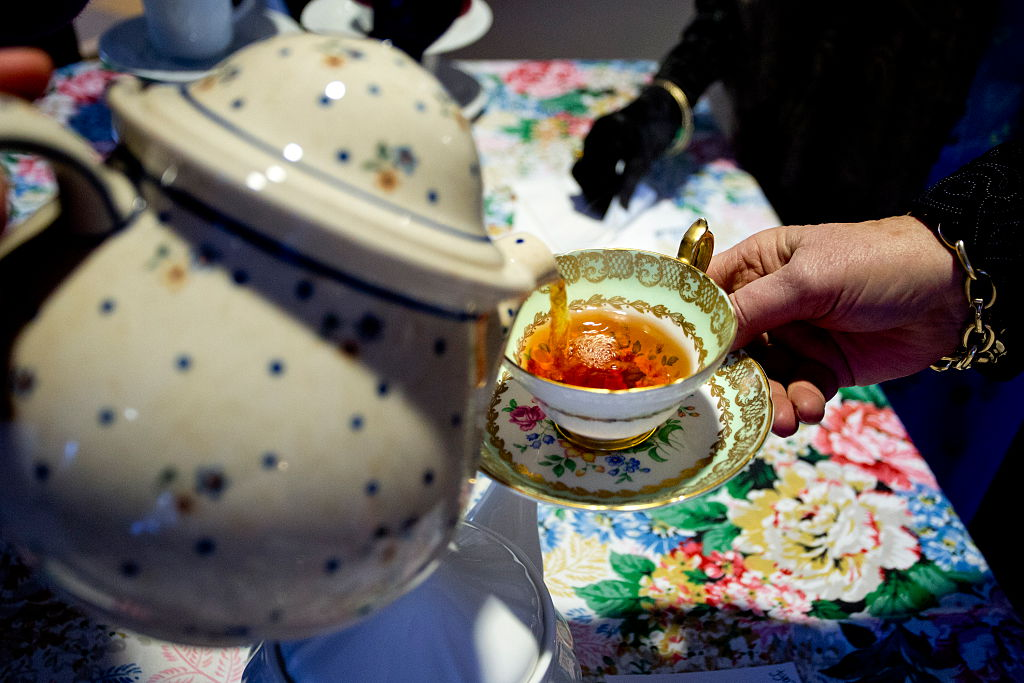 A tea cup is filled at a 'Downton Abbey' themed party