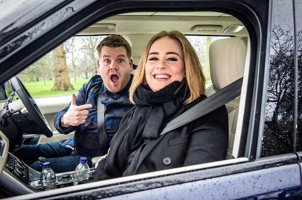 James Corden, in the driver's seat, excitedly pointing at Adele in the passenger seat of a car