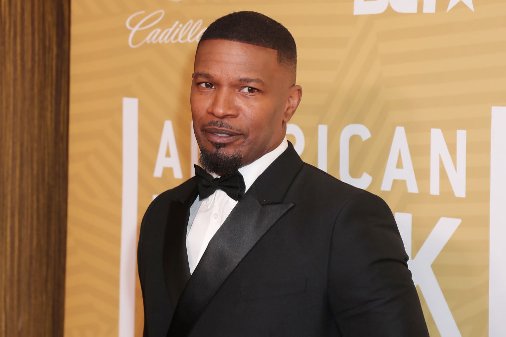 Jamie Foxx smiling in front of a repeating background