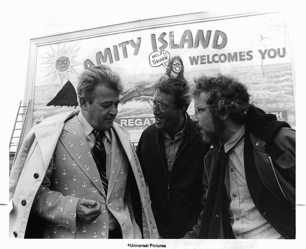Murray Hamilton, Roy Scheider, and Richard Dreyfuss standing in front of defaced billboard in a scene from the film 'Jaws', 1975
