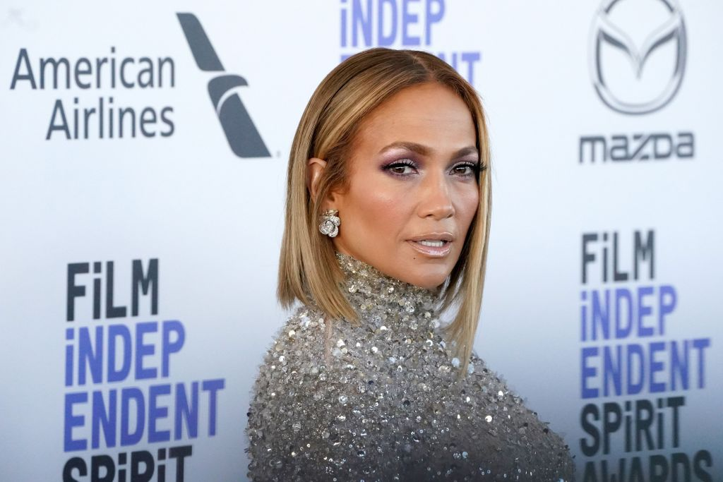 Jennifer Lopez smiling in front of a repeating background