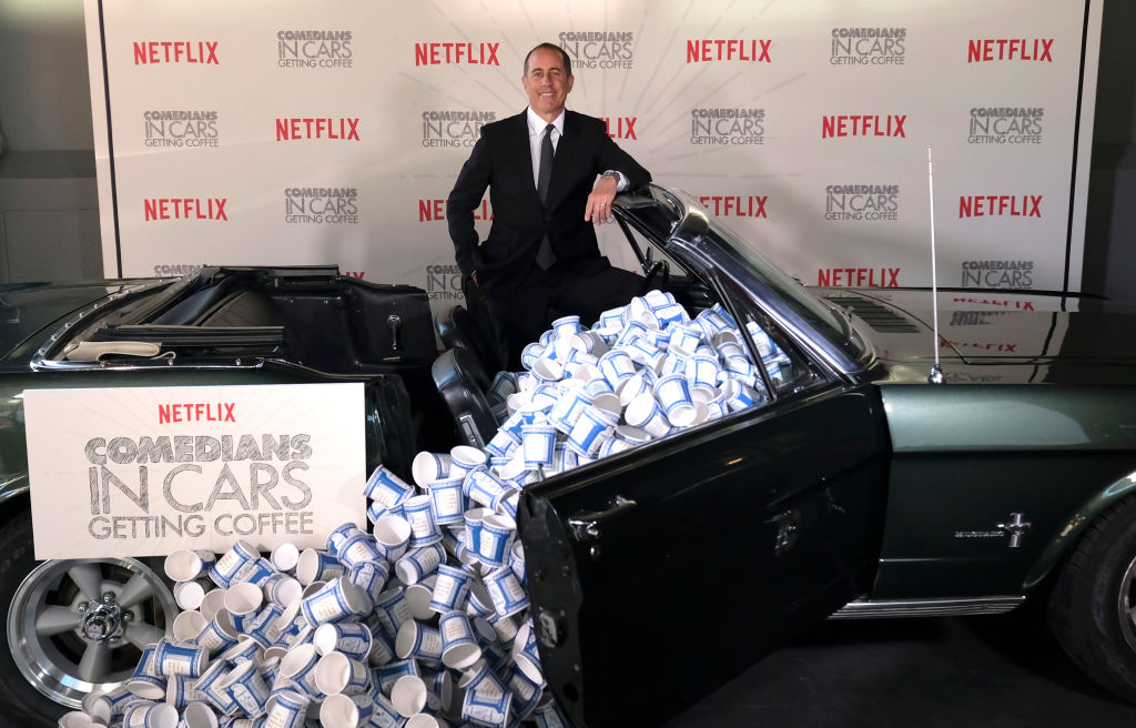 Jerry Seinfeld behind a prop car full of the classic New York to-go paper coffee cups