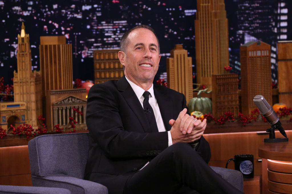 Jerry Seinfeld smiling in a chair