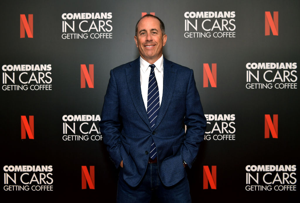 Jerry Seinfeld smiling in front of a repeating background