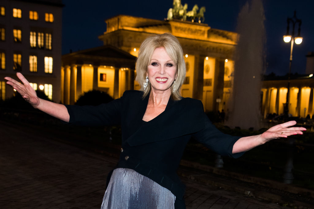 Joanna Lumley smiling with her arms outstretched