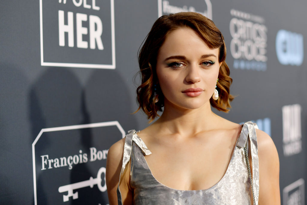 Joey King in front of a repeating background in a silver dress
