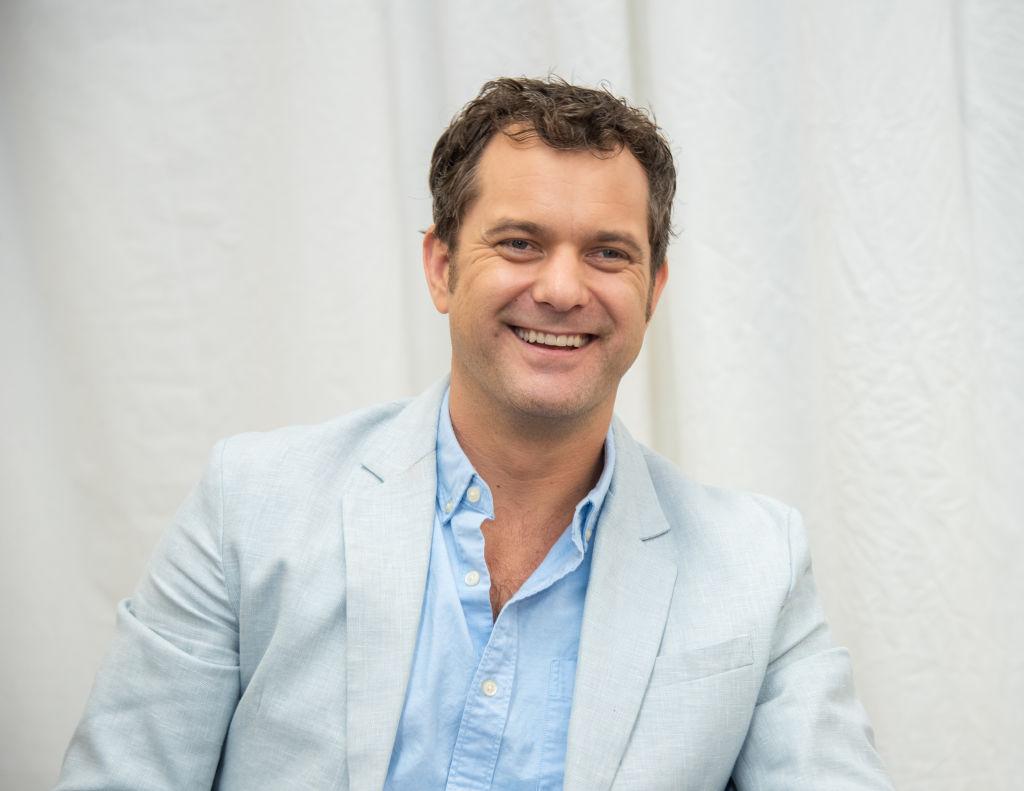 Joshua Jackson smiling in an off white jacket