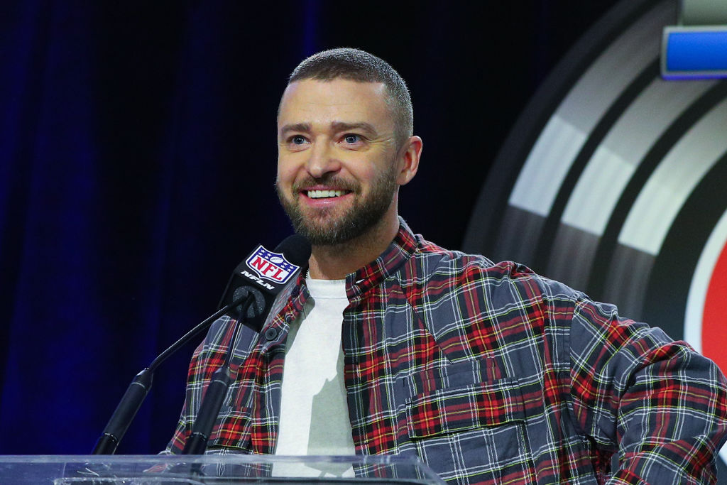 Justin Timberlake smiling in front of a mic with an NFL logo