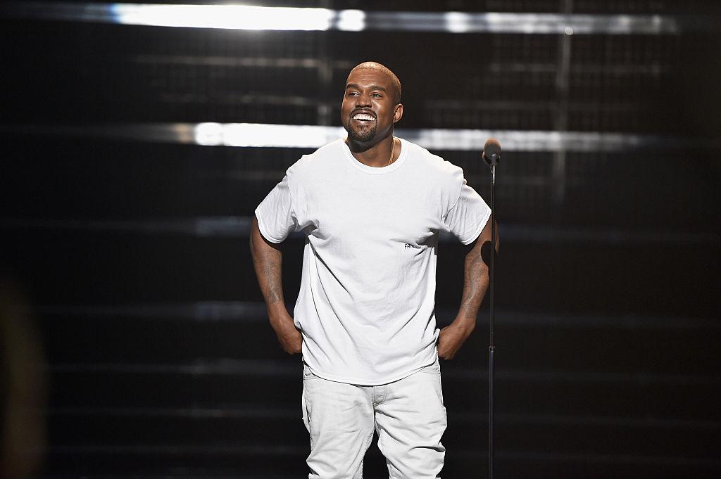 Kanye West smiling on stage