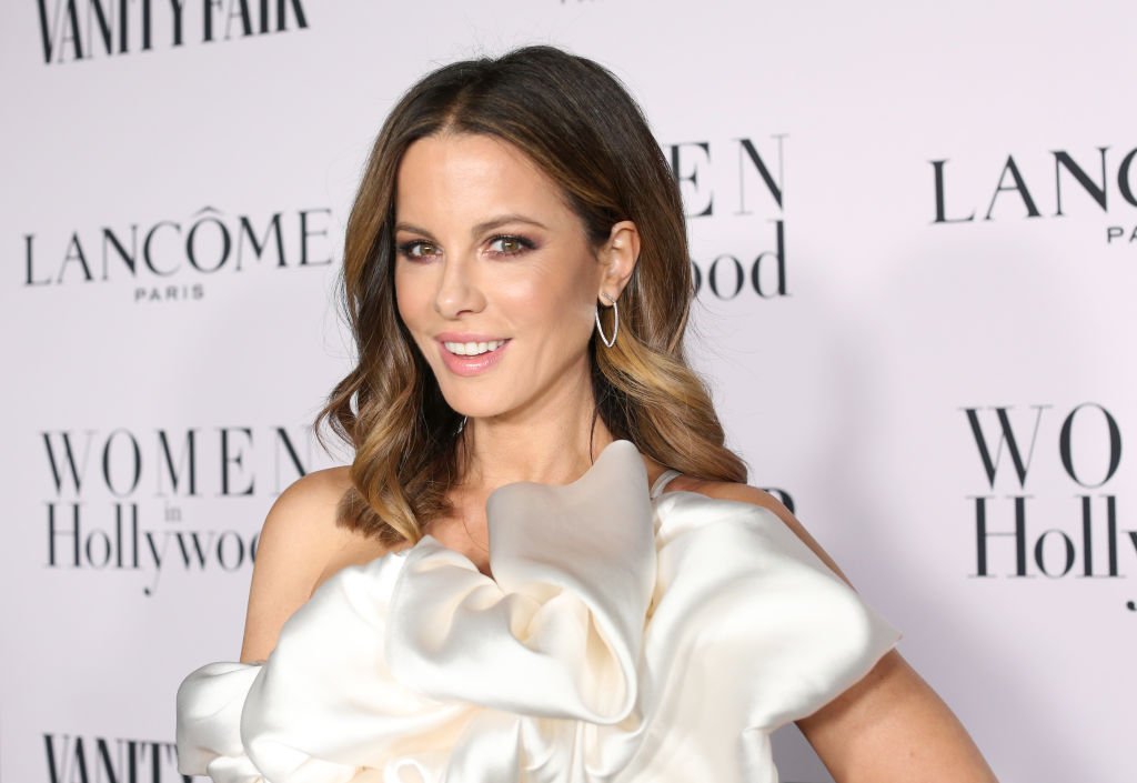 Kate Beckinsale smiling in front of a repeating background