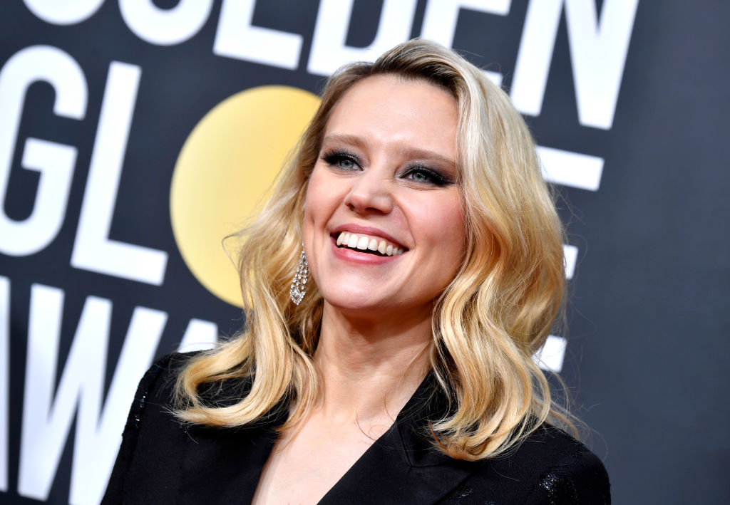 Kate McKinnon smiling in front of a repeating background