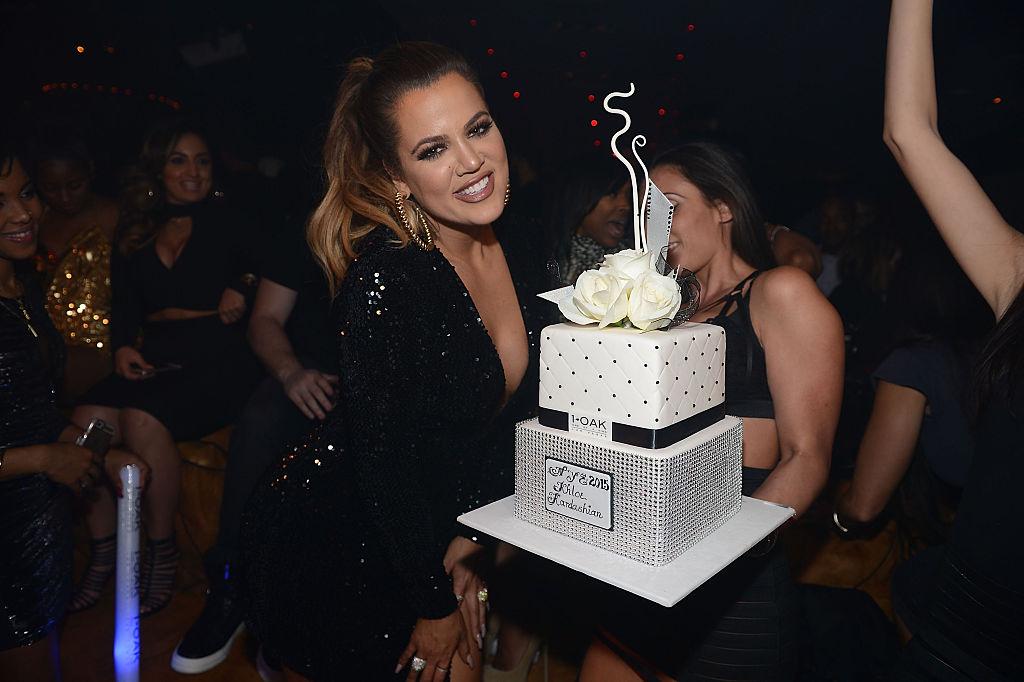Khloé Kardashian holding a large cake in a nightclub