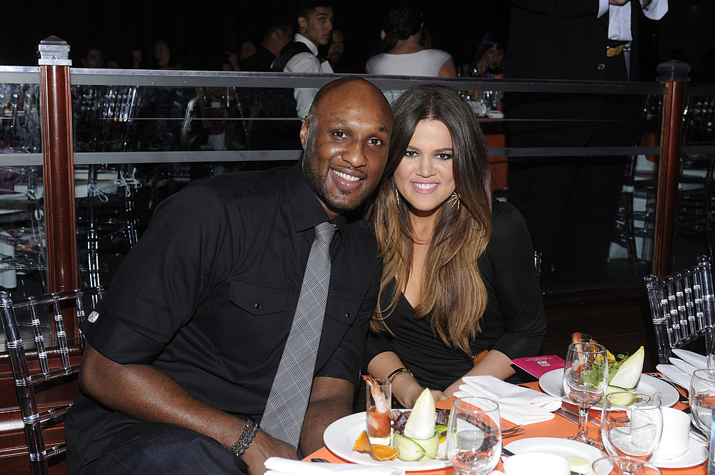 Lamar Odom and Khloé Kardashian smiling at dinner table