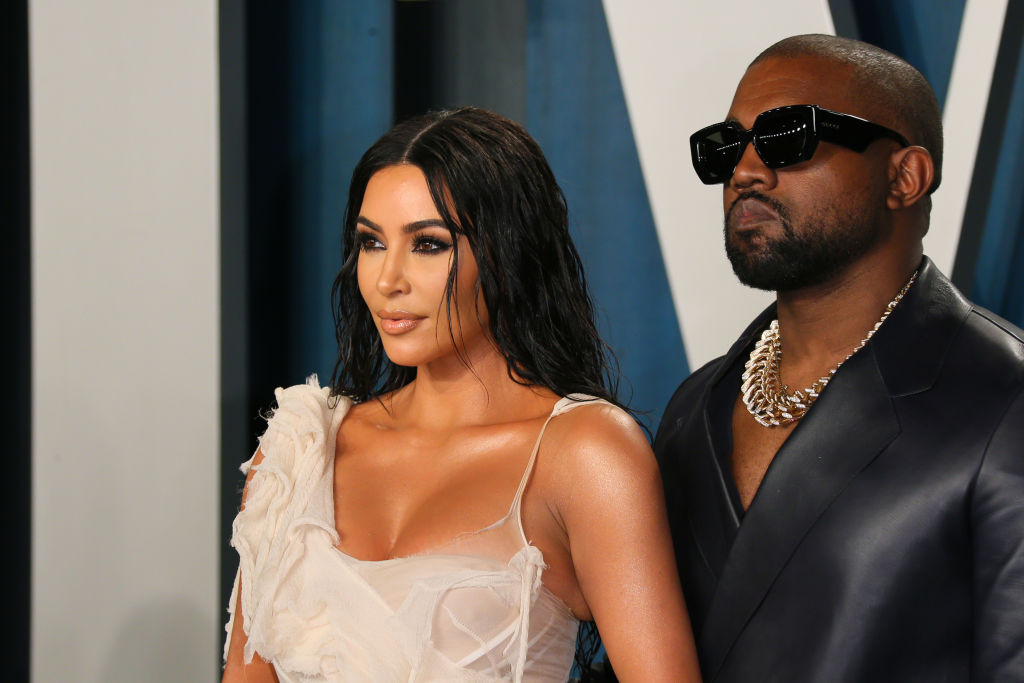 Kim Kardashian West and Kanye West smiling, looking away from the camera