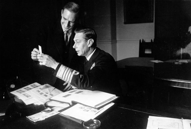 King George VI looks through stamps with the Curator of the Royal Stamp Collection