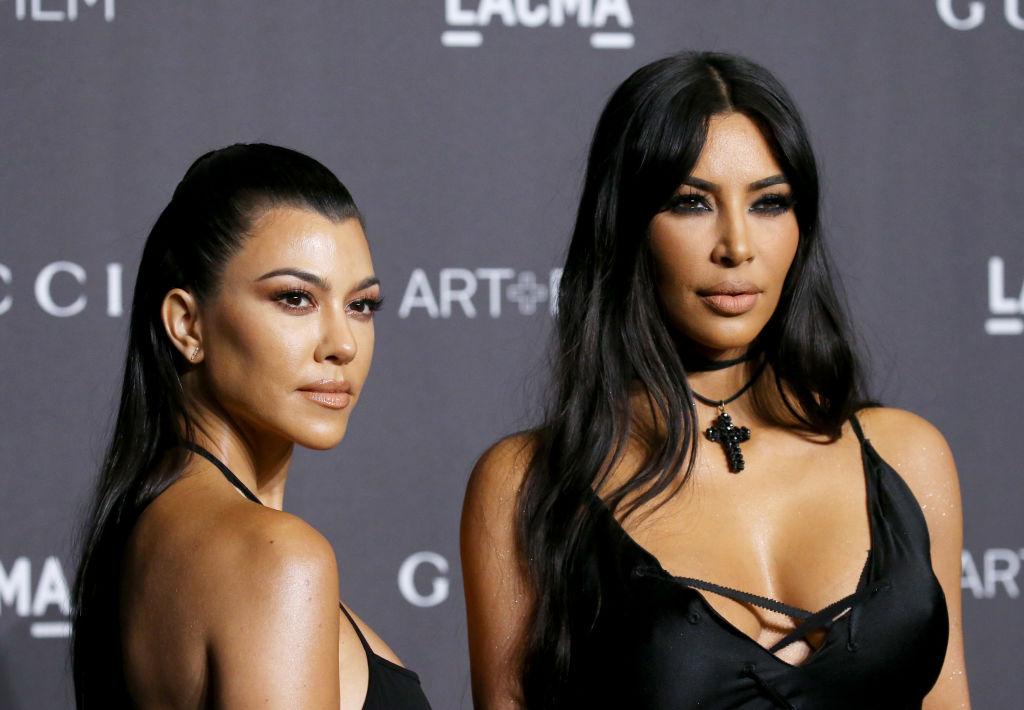Kourtney Kardashian and Kim Kardashian West in front of a repeating background