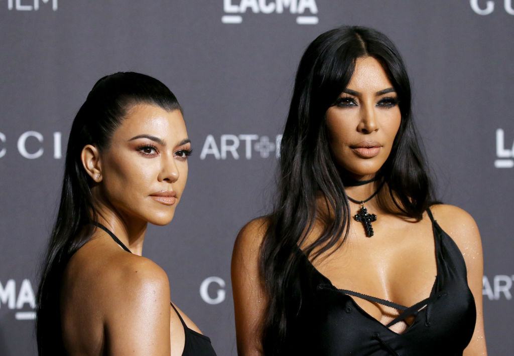 Kourtney Kardashian and Kim Kardashian West in front of a repeating background