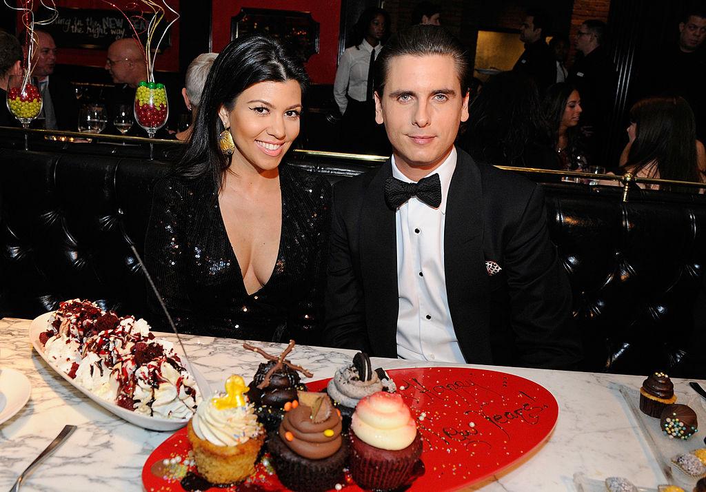 Kourtney Kardashian and Scott Disick in formalwear in front of desserts