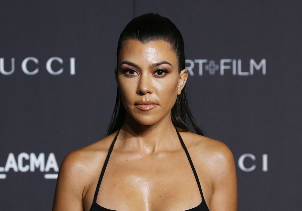 Kourtney Kardashian in front of a repeating background