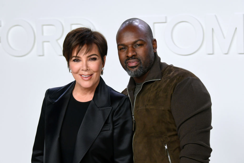 Kris Jenner and Corey Gamble smiling in front of a white background