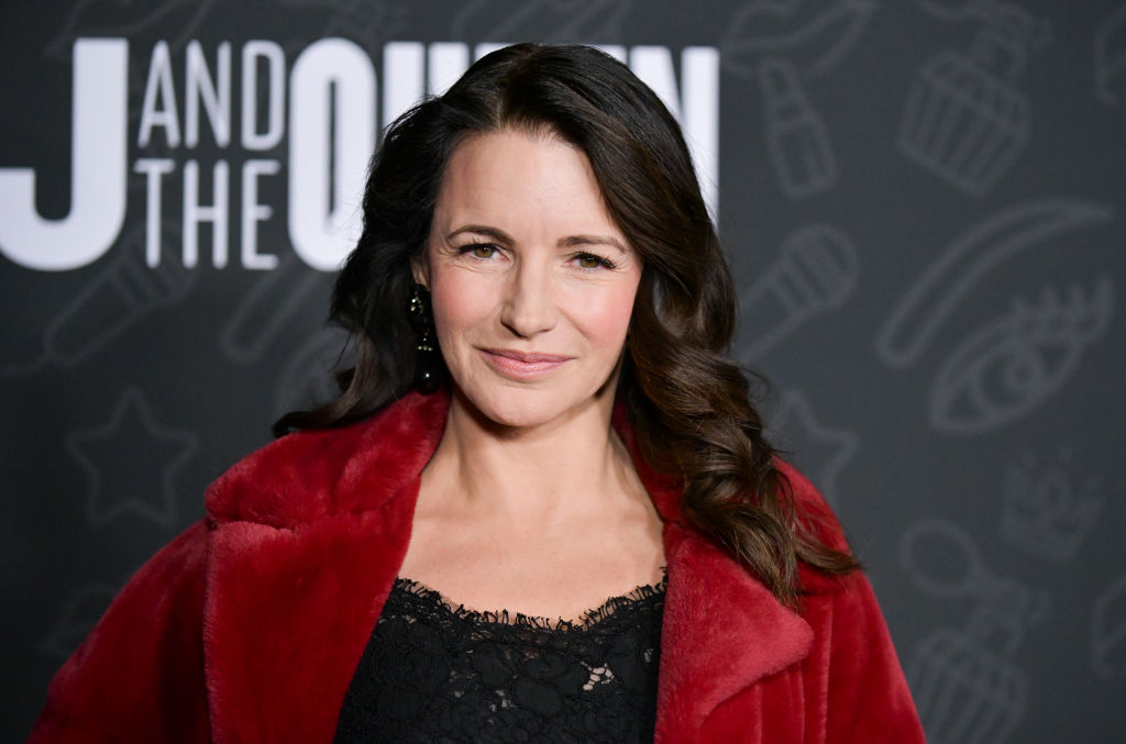 Kristin Davis smiling in front of a repeating background