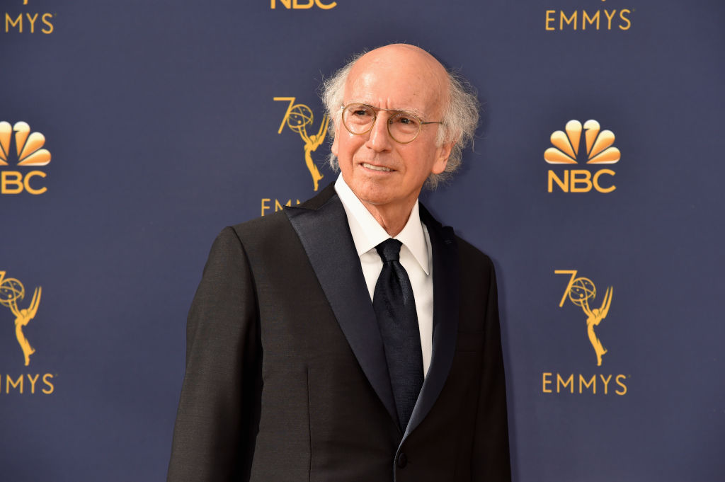 Larry David smiling off camera in front of an Emmy Awards' repeating backdrop