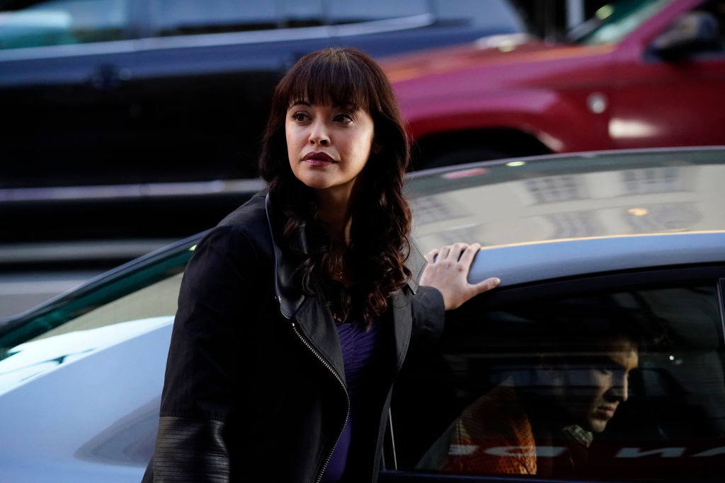Marisa Ramirez standing next to a car on set of 'Blue Bloods'