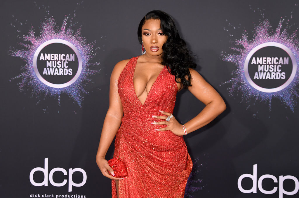 Megan Thee Stallion in a red dress in front of a repeating background