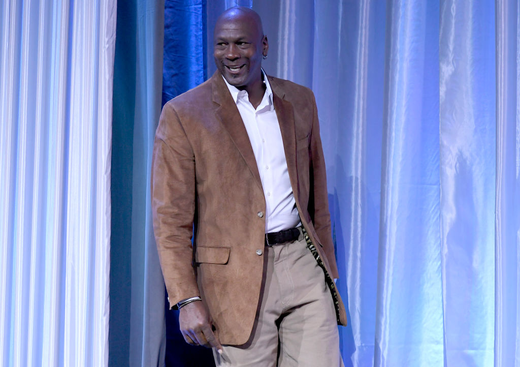 Michael Jordan smiling in a tan suit in front of a white curtain