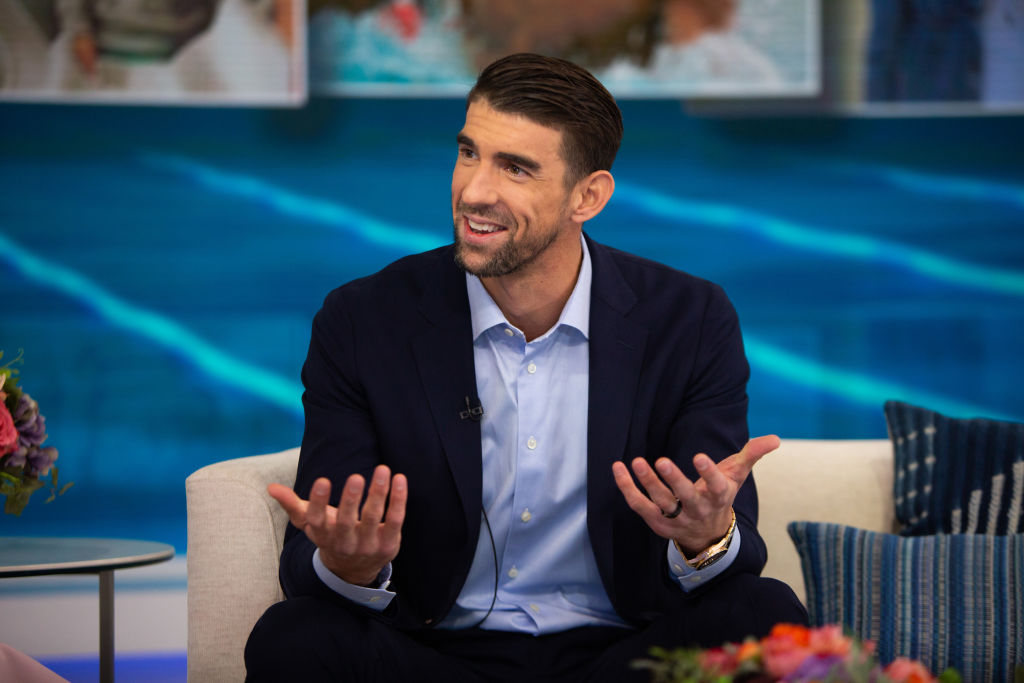 Michael Phelps, seated, smiling in front of a blue background