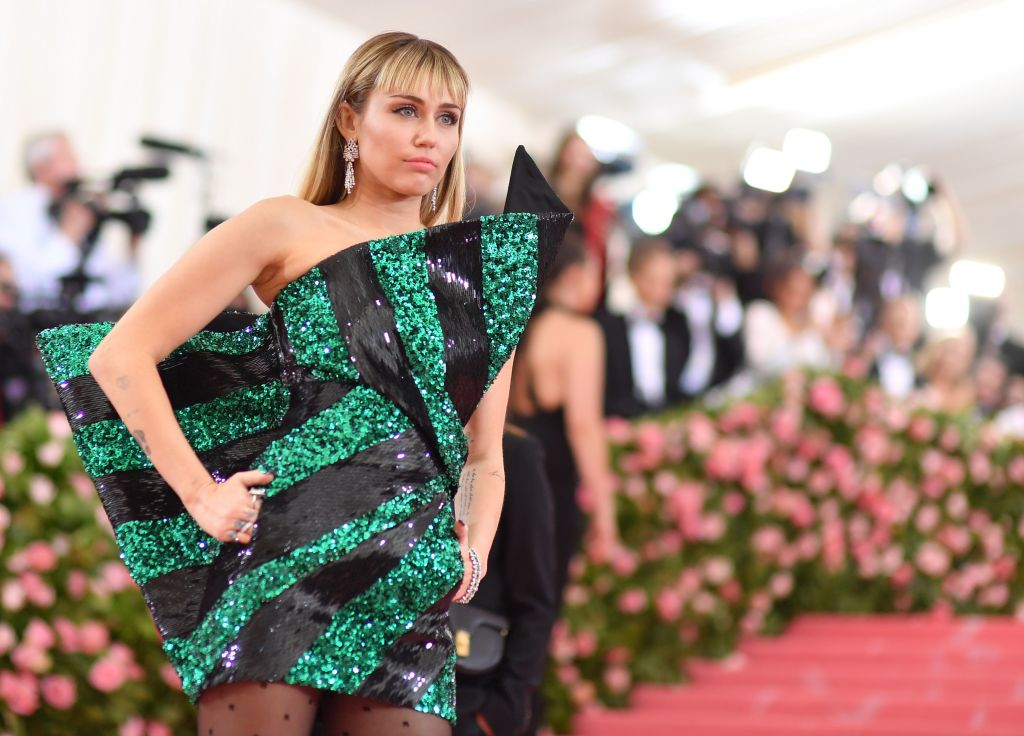 Miley Cyrus in a glitter green and black dress