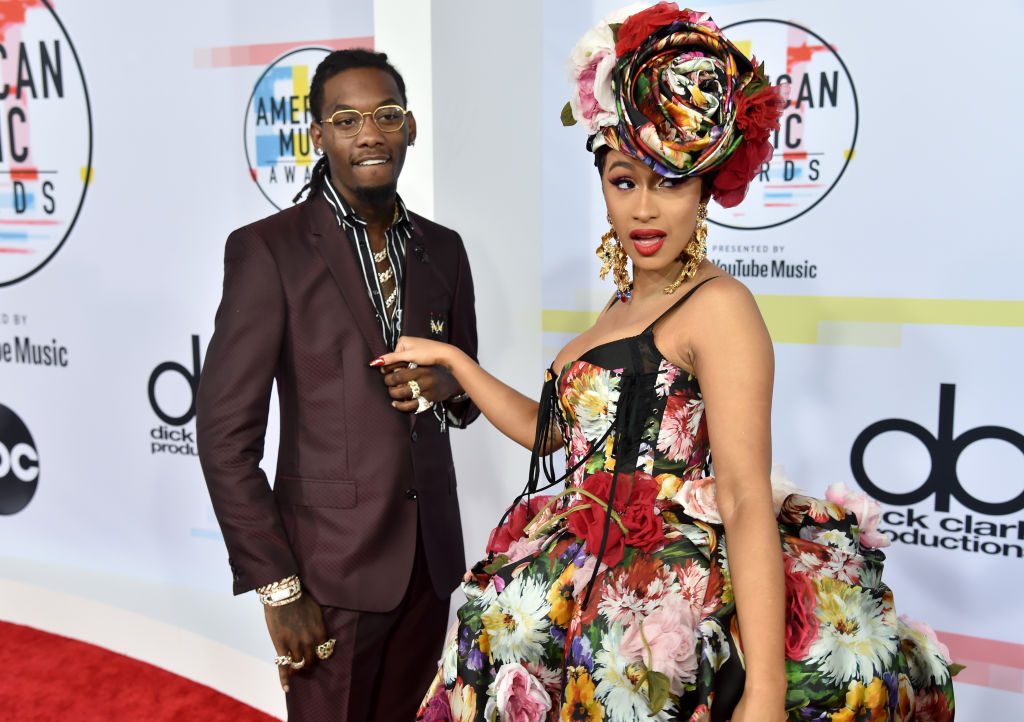 Offset and Cardi B holding hands looking away from the camera