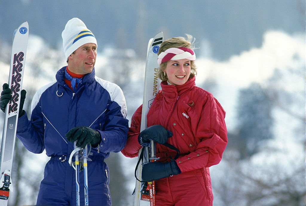"""incess Diana On A Ski-ing Holiday Together. The Princess Is Wearing A Red """"head"""" Ski Suit And A Headband And She Is Holding A Pair Of """"dynamic"""" Skis.  The Prince Is Wearing A Blue Ski Suit And Carrying A Pair Of """"k2"""" Skis."""